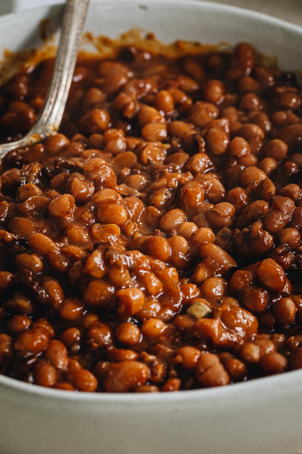 close up of smoked baked beans in a large bowl with silver serving spoon