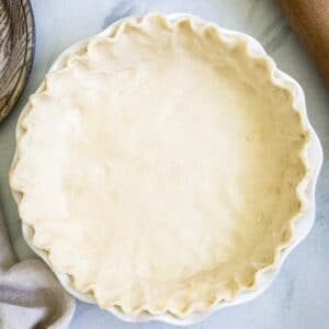 Buttermilk pie crust in a white pie dish on marble surface.