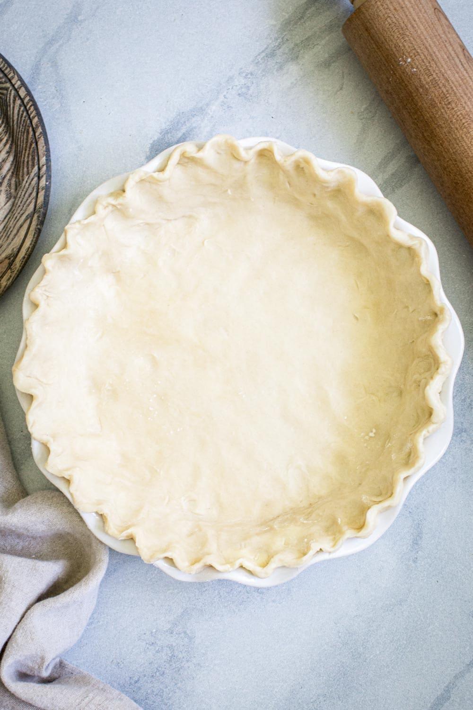 buttermilk pie crust in a white pie dish on marble surface