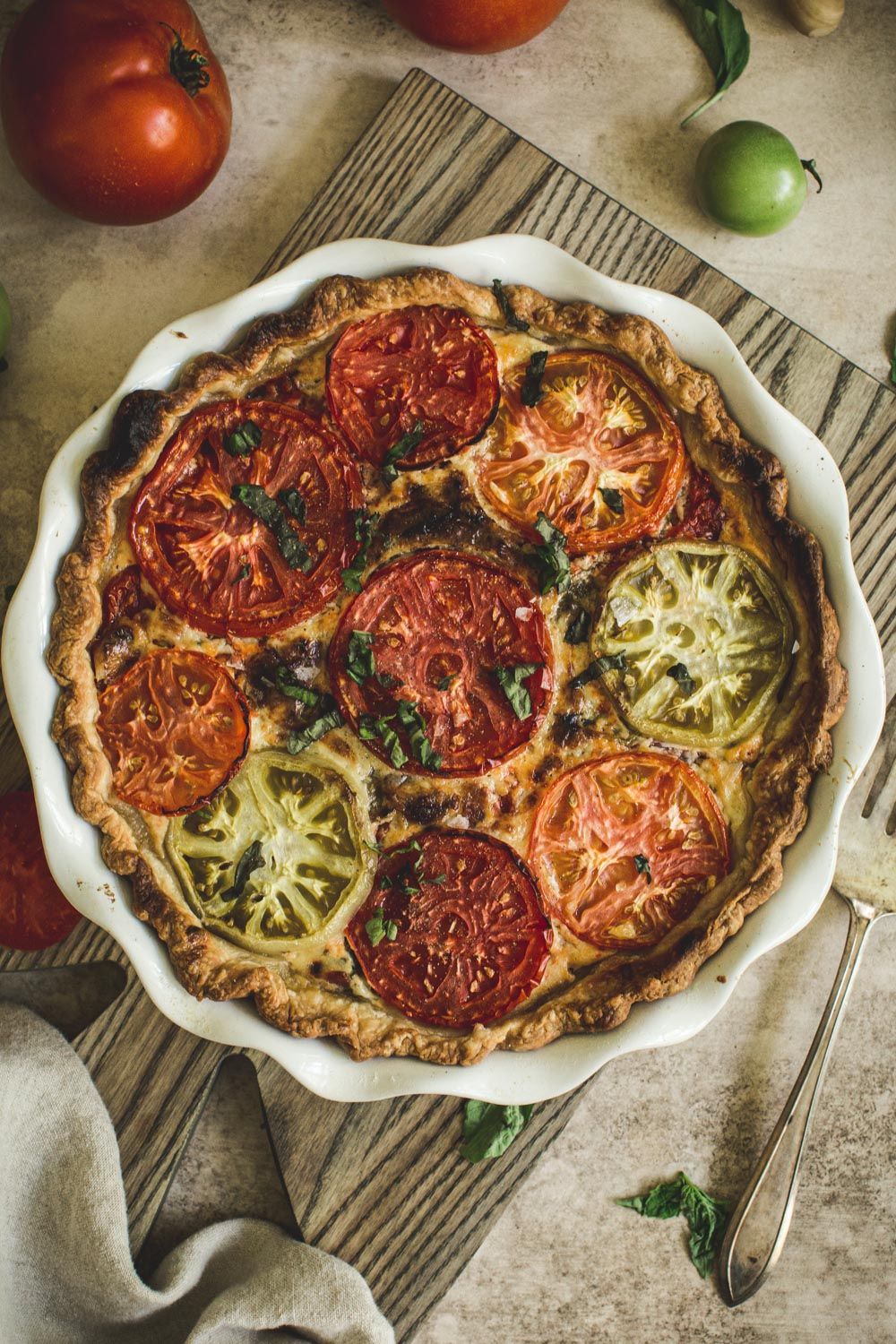 tomato pie in a white pie dish on top of a wooden cutting board