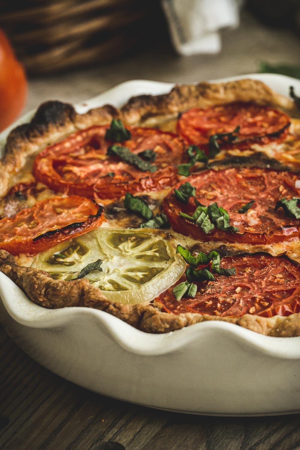 side view of tomato pie topped with fresh basil