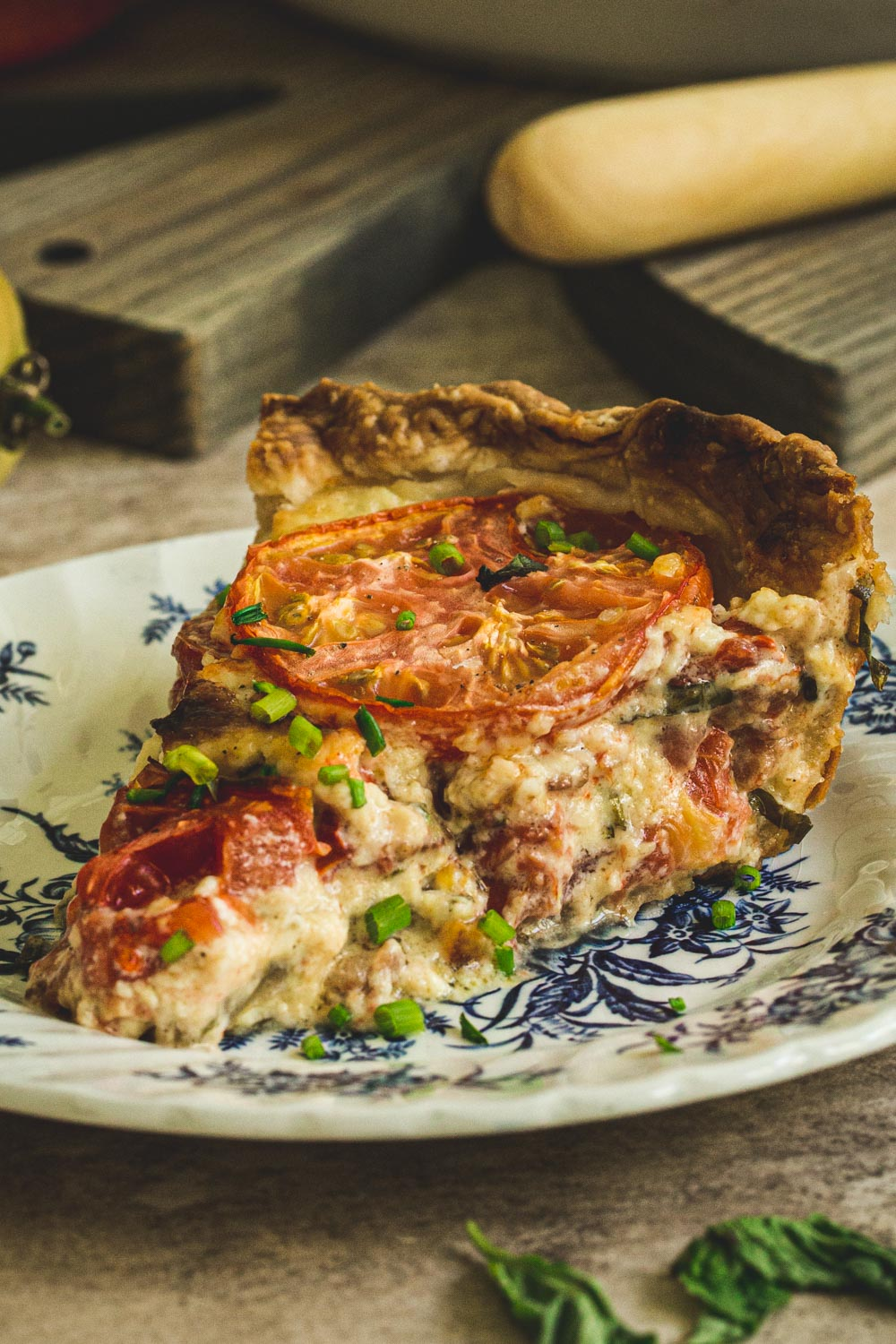 slice of tomato pie topped with chives on a blue and white plate