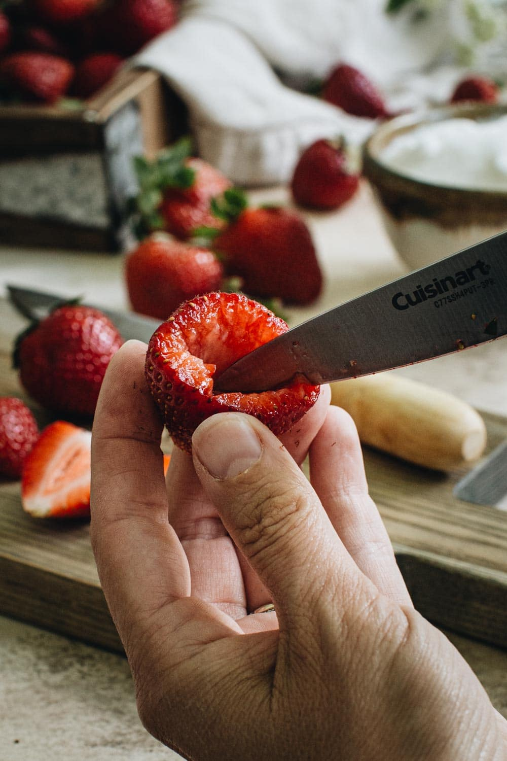hand holding a hulled strawberry with knife pointed towards center of hull