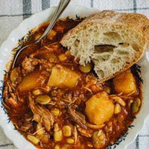 Brunswick Stew in a white and blue bowl with spoon and bread slice. White title with orange background.