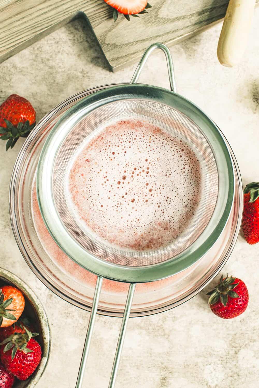Mesh sieve with strawberry puree draining.