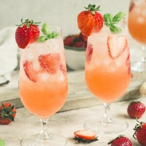 Two strawberry mojitos in tall glasses topped with sliced strawberries and basil leaves.