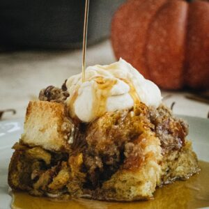 Square slice of french toast casserole with whipped cream and syrup being poured on top.