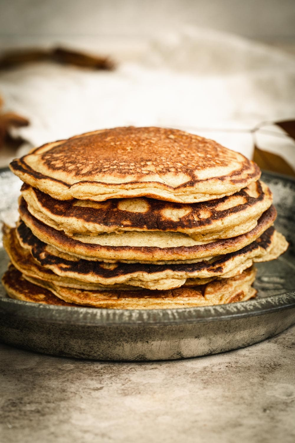 Plain stack of pumpkin pancakes in a metal pie tin.