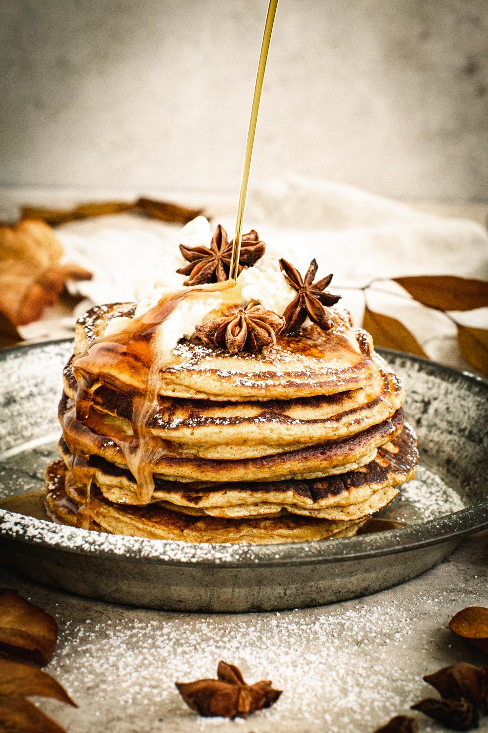Syrup drizzling on top of pumpkin pancakes topped with whipped cream, powdered sugar, and star anise.