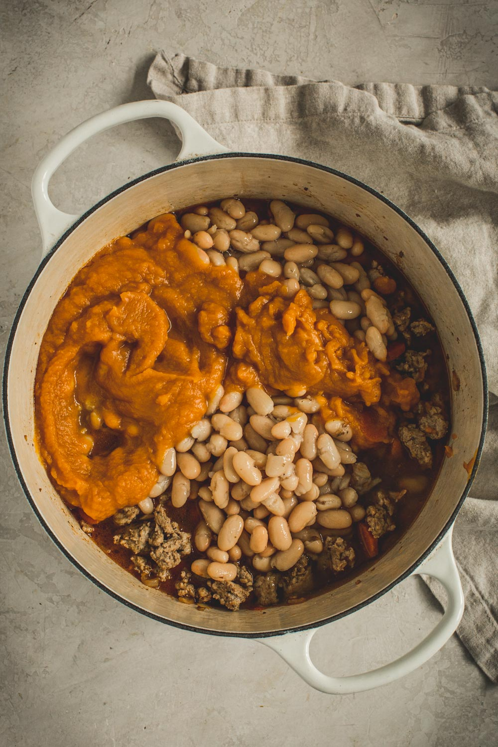 Adding the pumpkin and white beans to the chili.