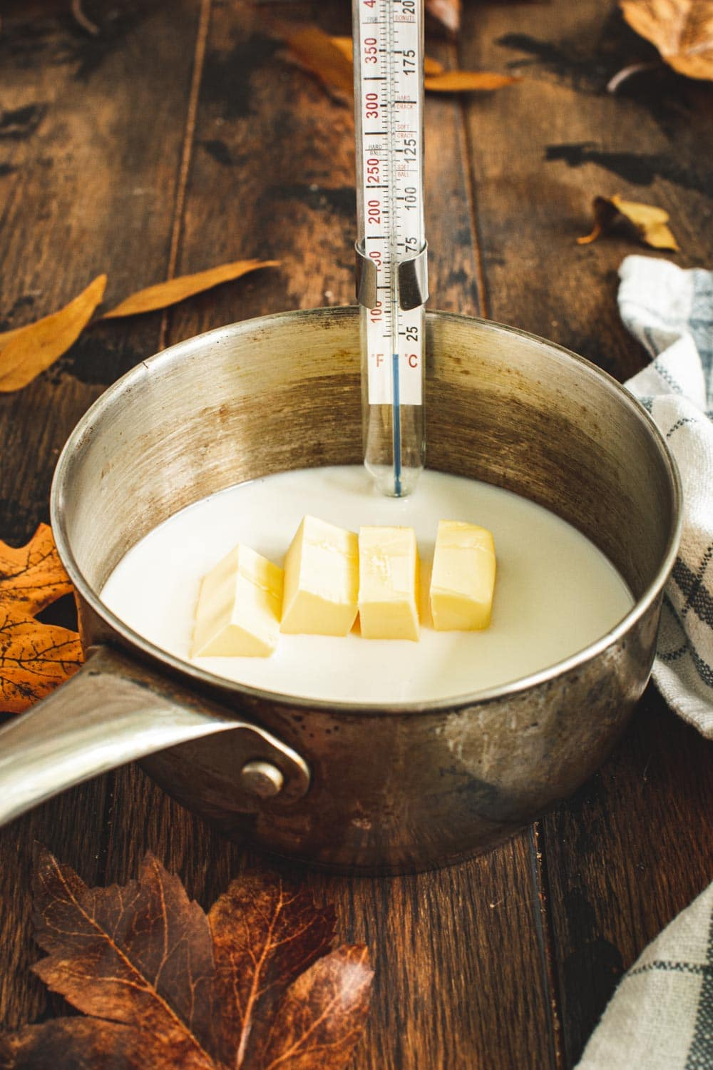 Milk mixture ingredients in small saucepan with candy thermometer clipped to the side.