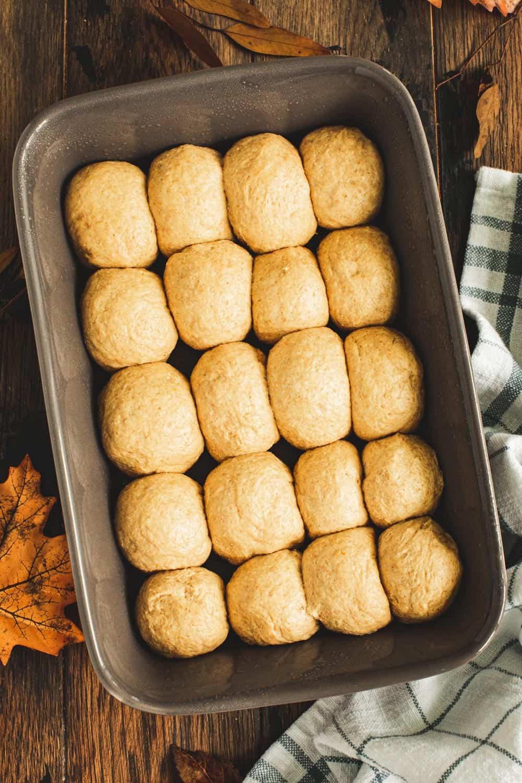 Unbaked pumpkin dinner rolls in a gray baking dish.