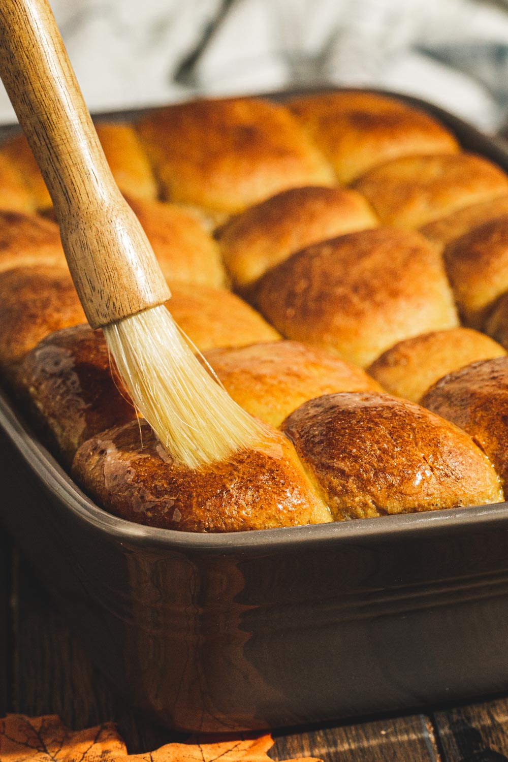 Brushing pumpkin dinner rolls in a gray baking dish with butter.