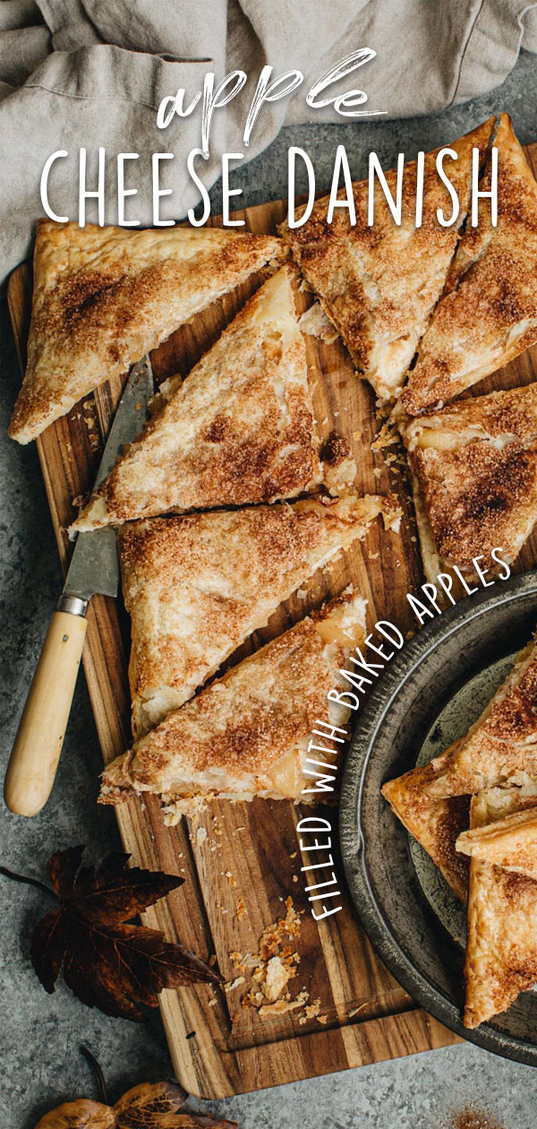 Apple cheese danishes sliced into triangles on a cutting board with a knife.