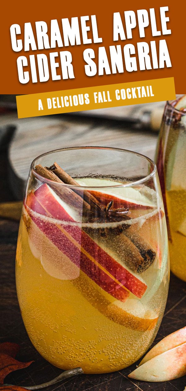 Caramel apple cider sangria in a stemless glass with apple slices and a cinnamon stick. Pinterest image with white title.