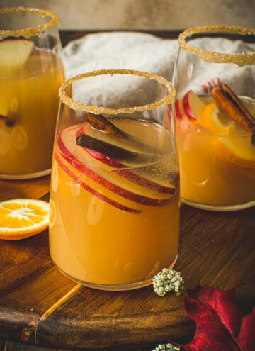 Glass of caramel apple sangria with a caramel and sugar coated rim.