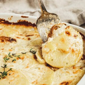 Scalloped potatoes in a white dish with a silver serving fork taking out a serving.