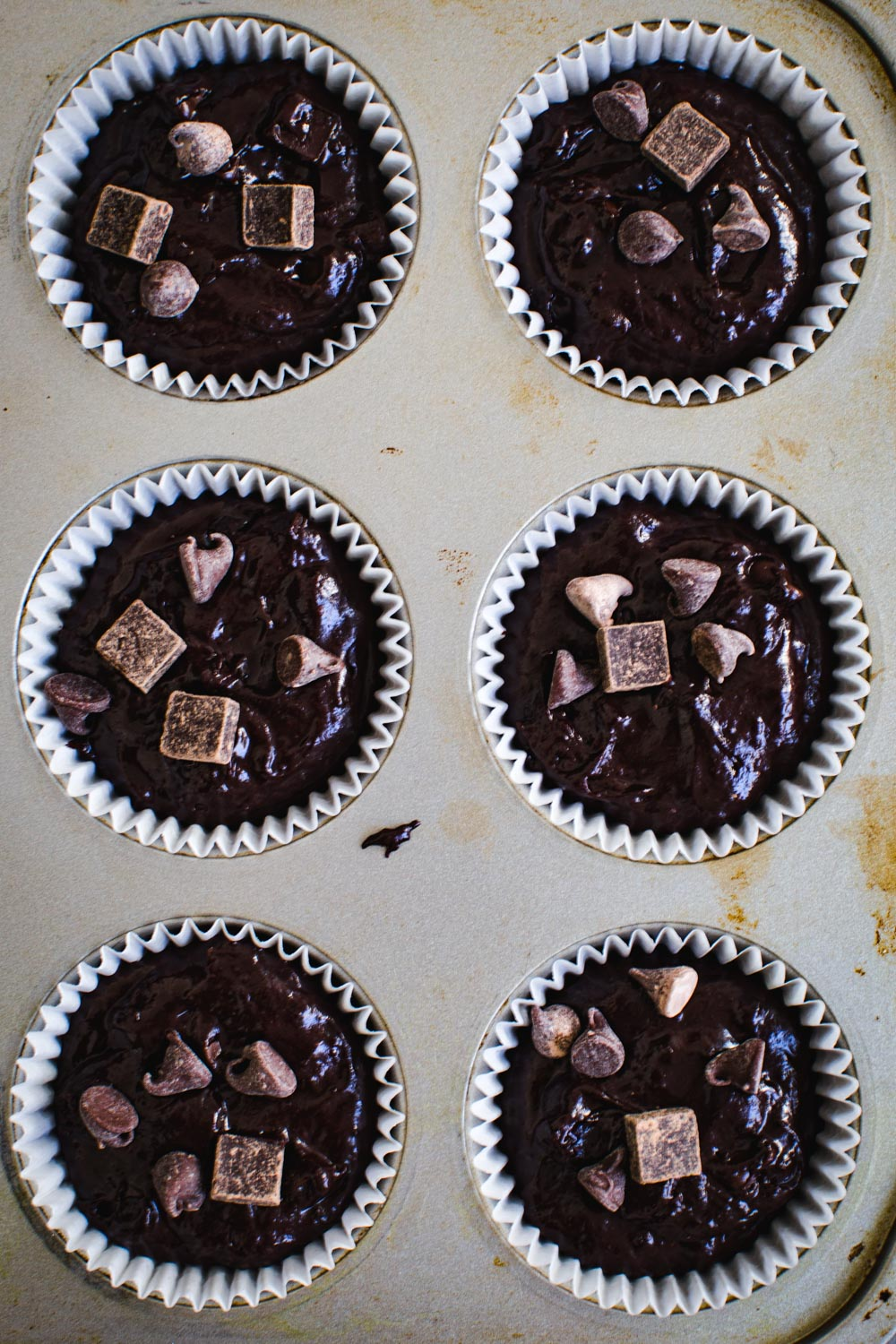 Double chocolate chip muffin batter in muffin tin.