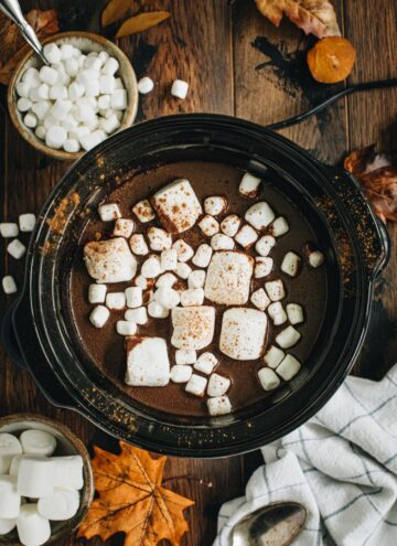 Pumpkin hot chocolate in the slow cooker topped with big and small marshmallows and cinnamon.