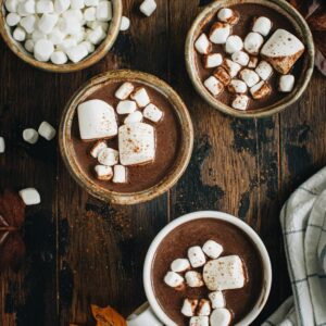 Three cups of pumpkin hot chocolate topped with marshmallows next to a bowl of mini marshmallows.