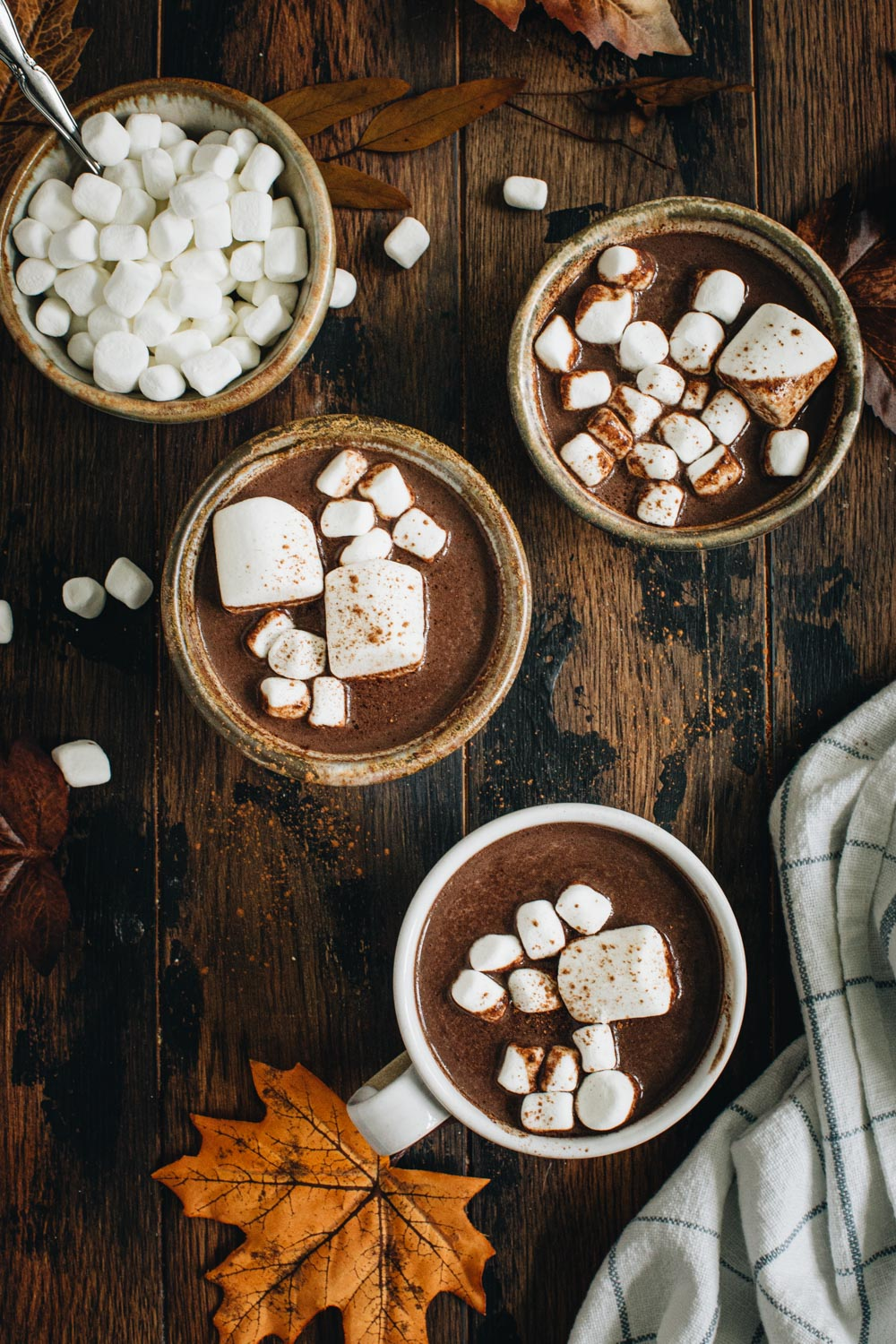 Three cups of pumpkin hot chocolate topped with marshmallows on a wooden table with a bowl full of mini marshmallows.