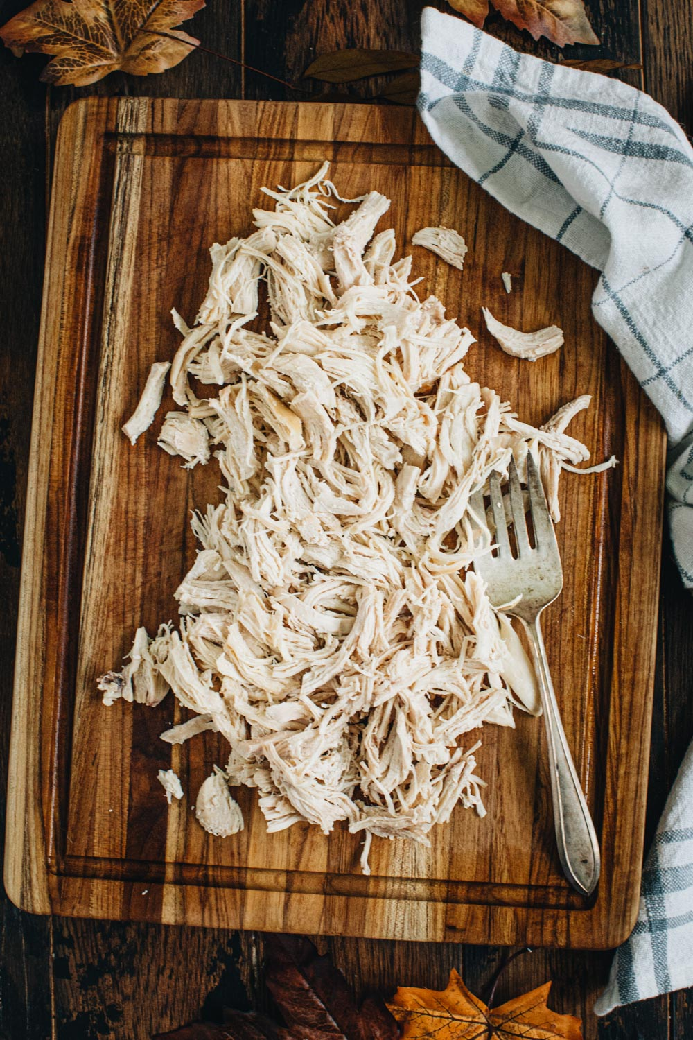 Pulled chicken on a wooden cutting board with a serving fork.
