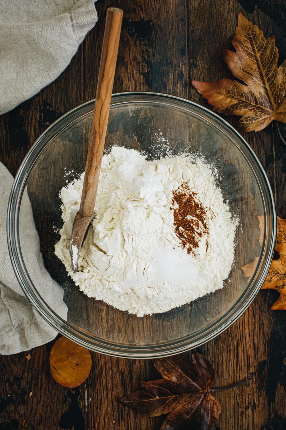 Dry ingredients for chocolate and pumpkin brownies in a mixing bowl with a wooden spoon.