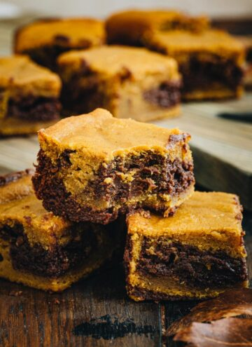 Chocolate and Pumpkin Brownies stacked on top of each other with a bite taken out of one.