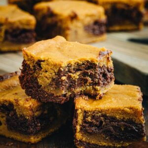 Pumpkin swirl brownies stacked on top of each other.