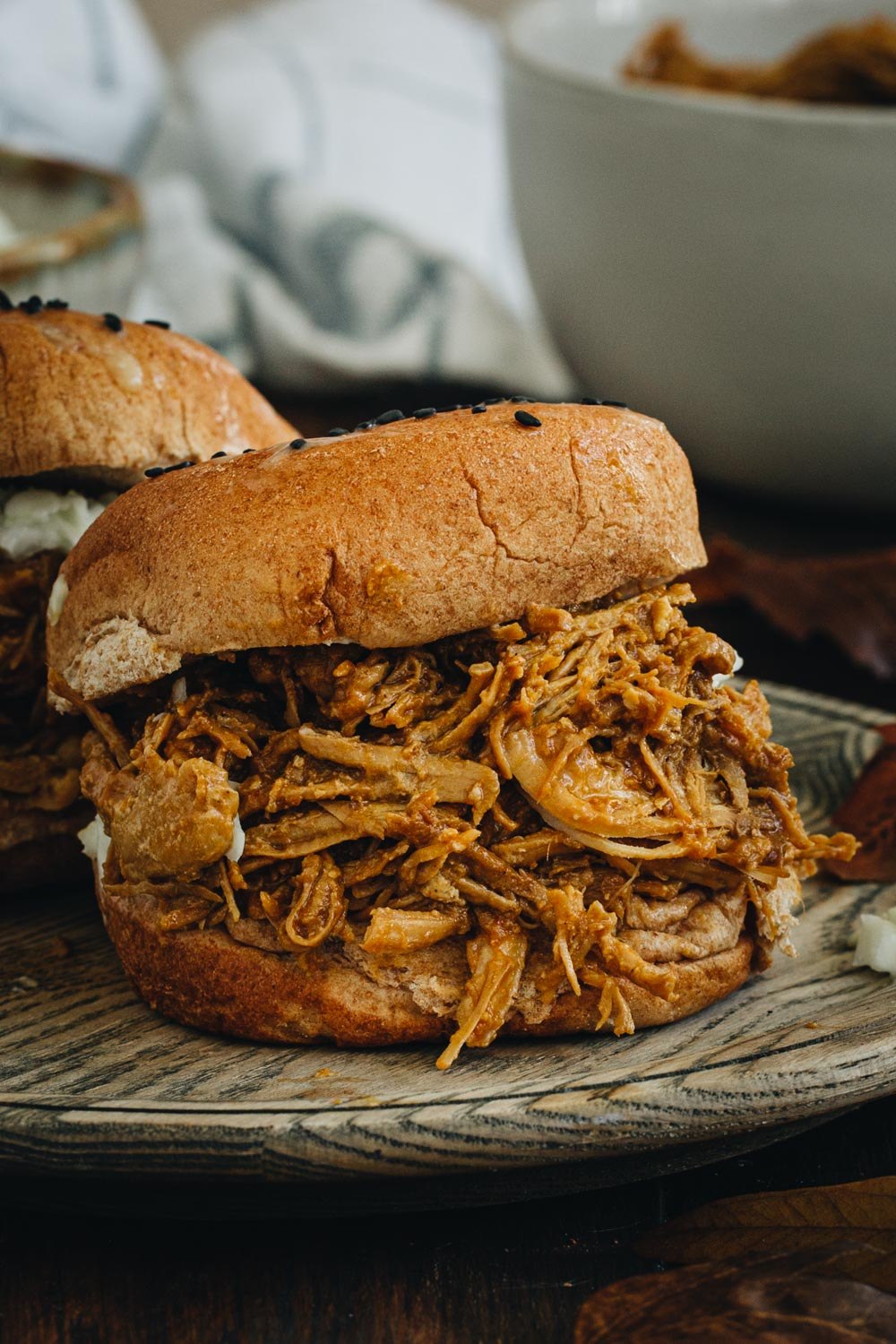 Close up of bbq chicken slider sitting on a wooden plate.