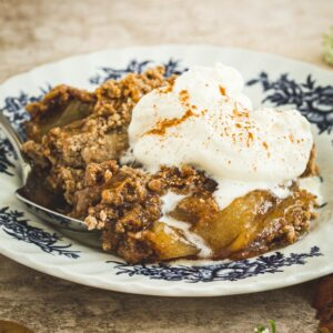 Apple dump cake on a white and blue plate topped with cinnamon whipped cream.