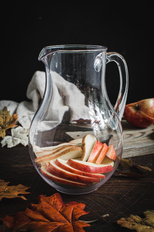 Apple cider sangria fruit in glass pitcher.