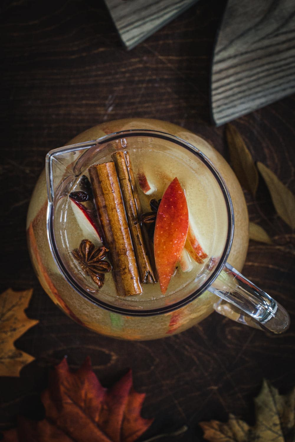 Top view of sangria in a pitcher  topped with fruit, cinnamon sticks, and star anise.