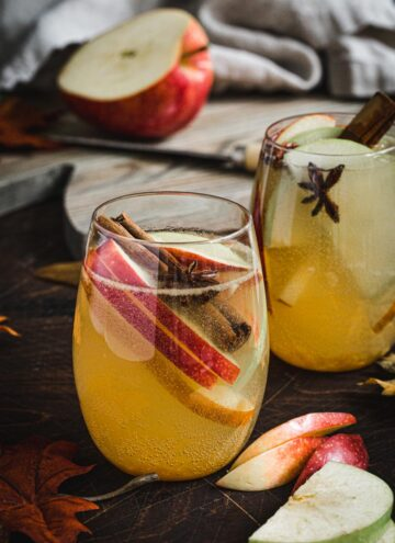 Apple cider sangria with fruit in a stemless wine glass.