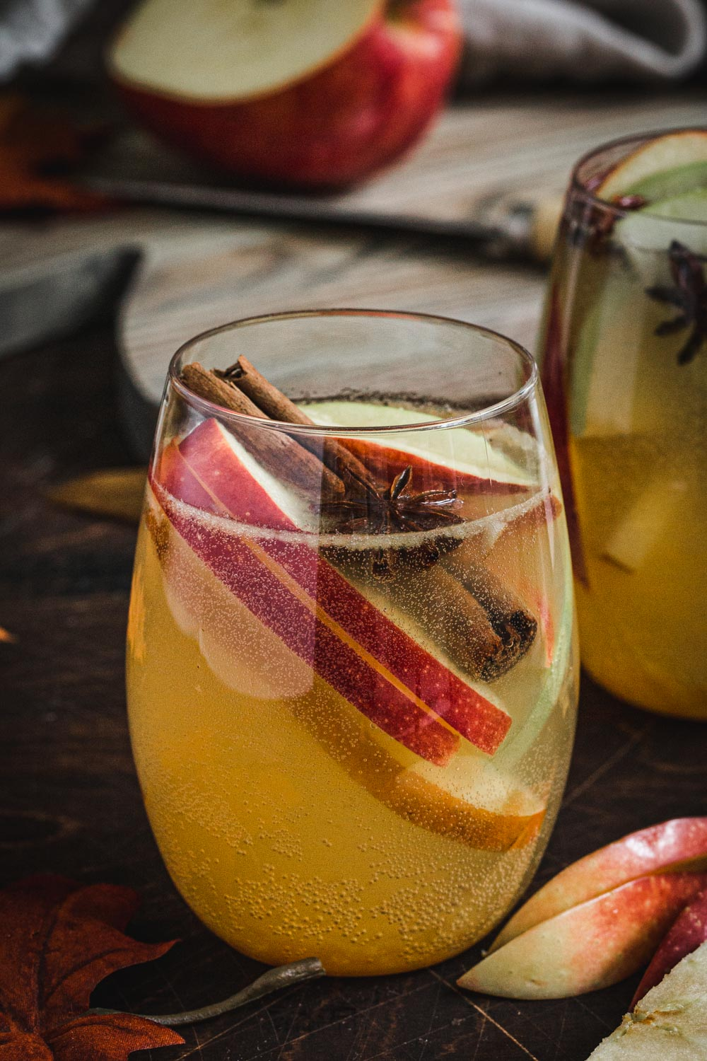 Caramel apple cider sangria with apple slices, cinnamon stick, and star anise.