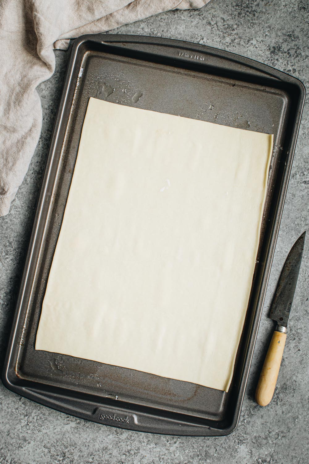Plain pastry on a rimmed baking sheet.