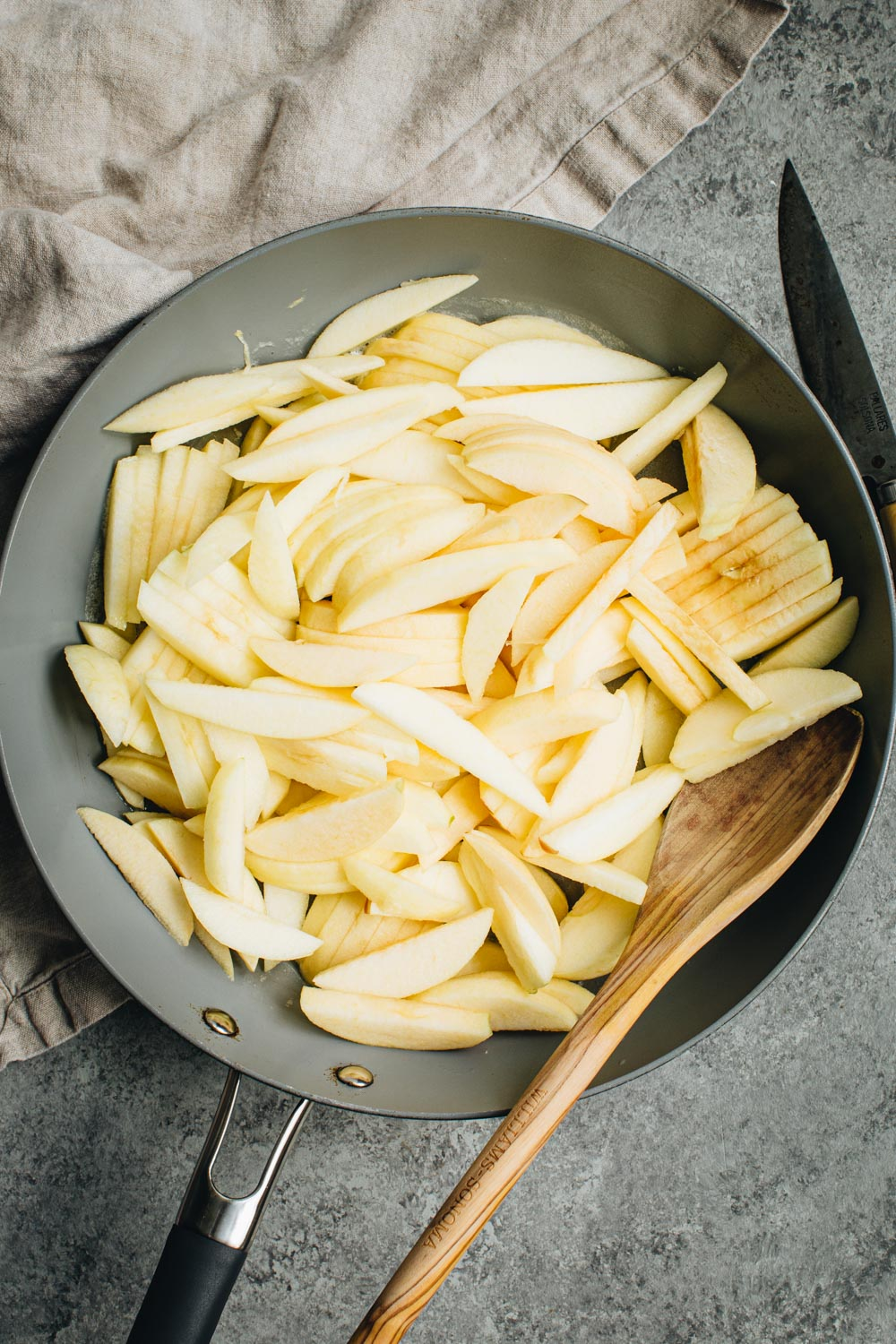 Sliced apples in a skillet with a wooden spatula.