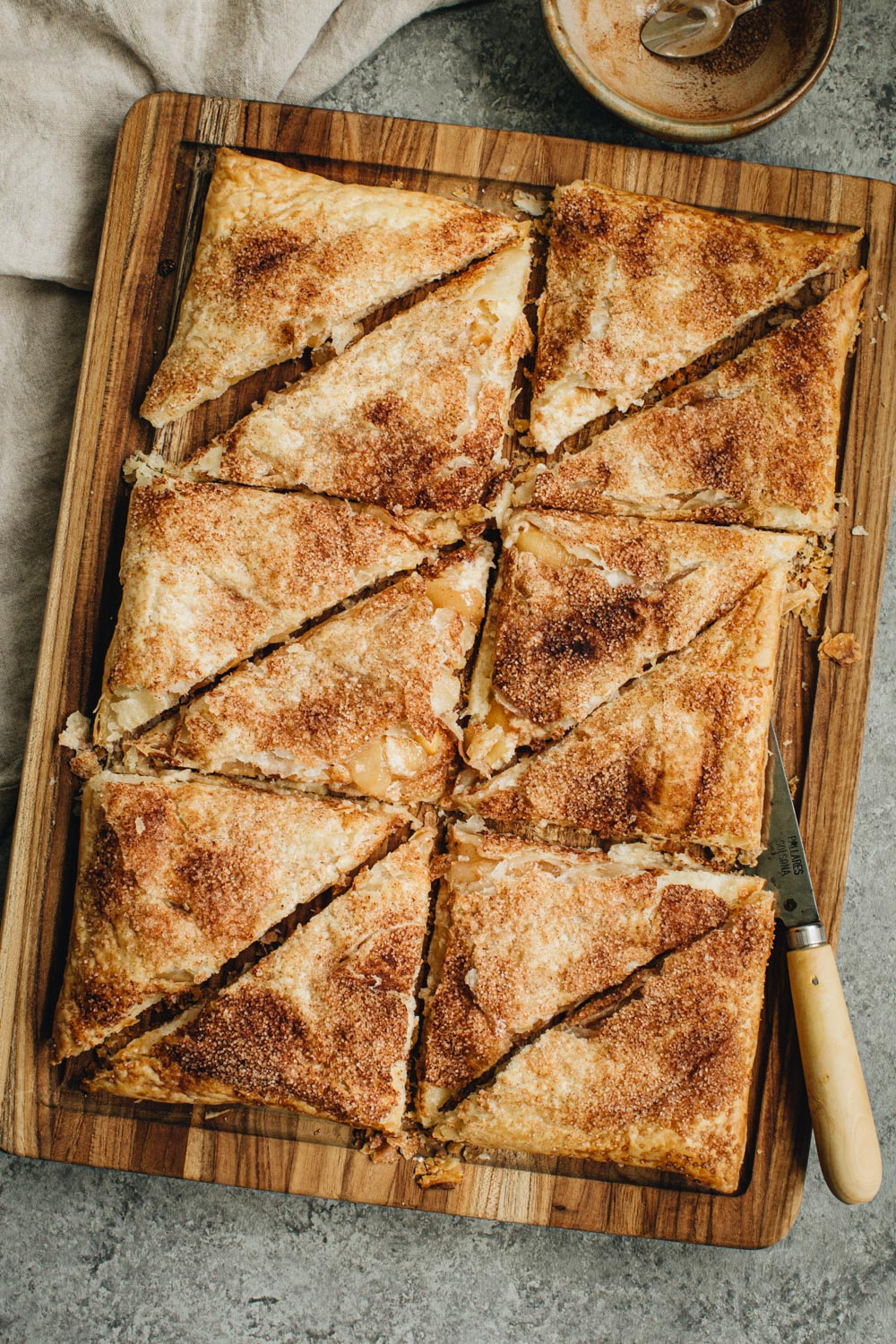 Sliced Apple Cheese Danishes on wooden cutting board.