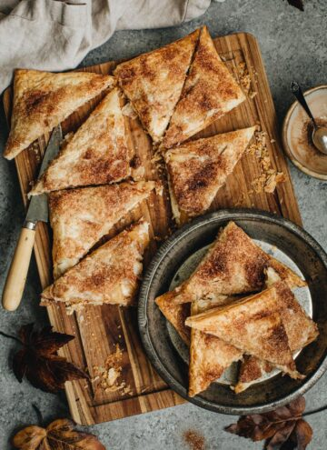 Apple cheese danishes sliced into triangles on a wooden cutting board and in a metal pie tin.
