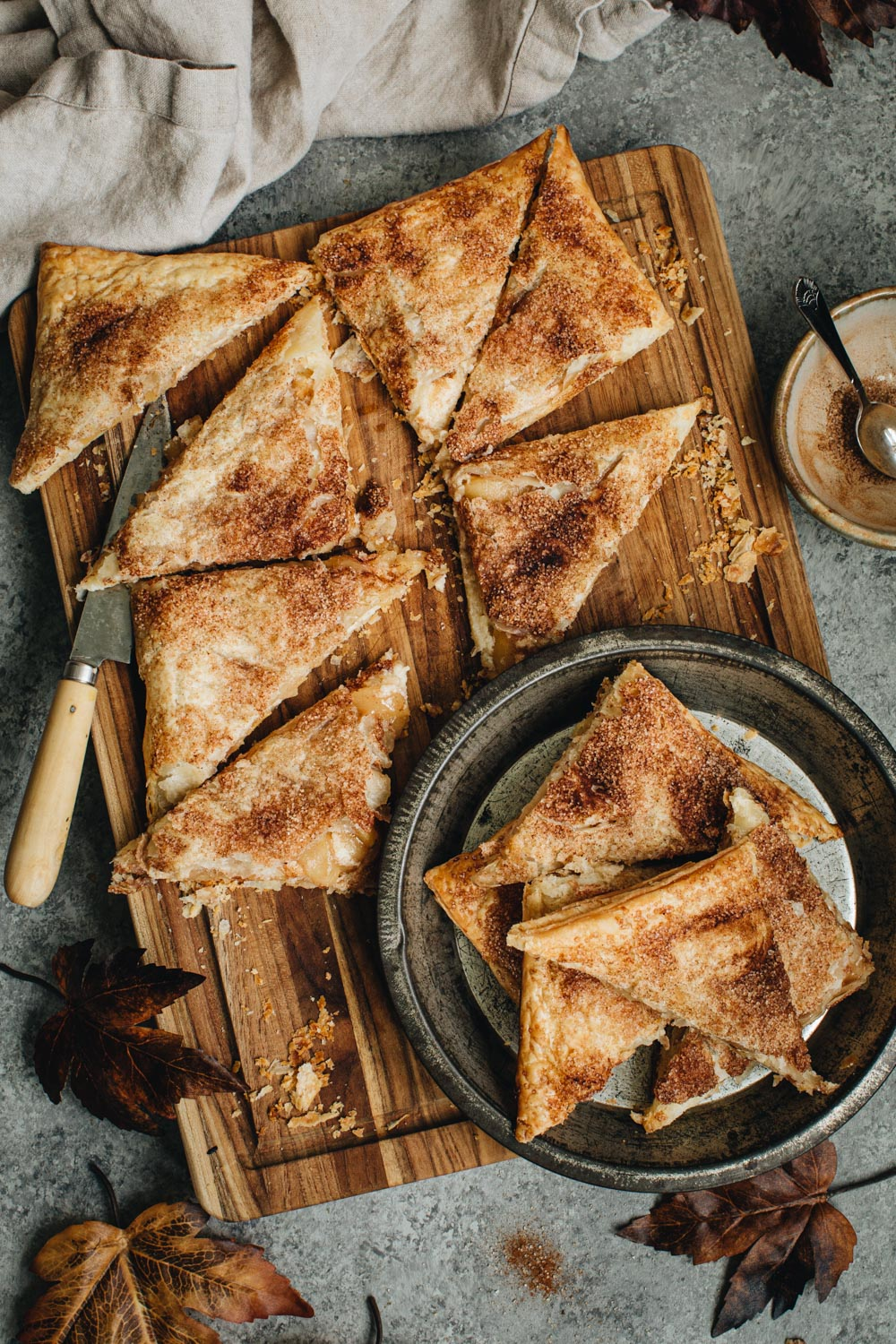 Apple cheese danish sliced into a triangle shape on a wooden cutting board and on a metal tin.
