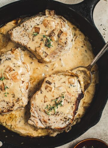 Pork chopes in a creamy apple cider sauce topped with fresh thyme in an iron skillet.