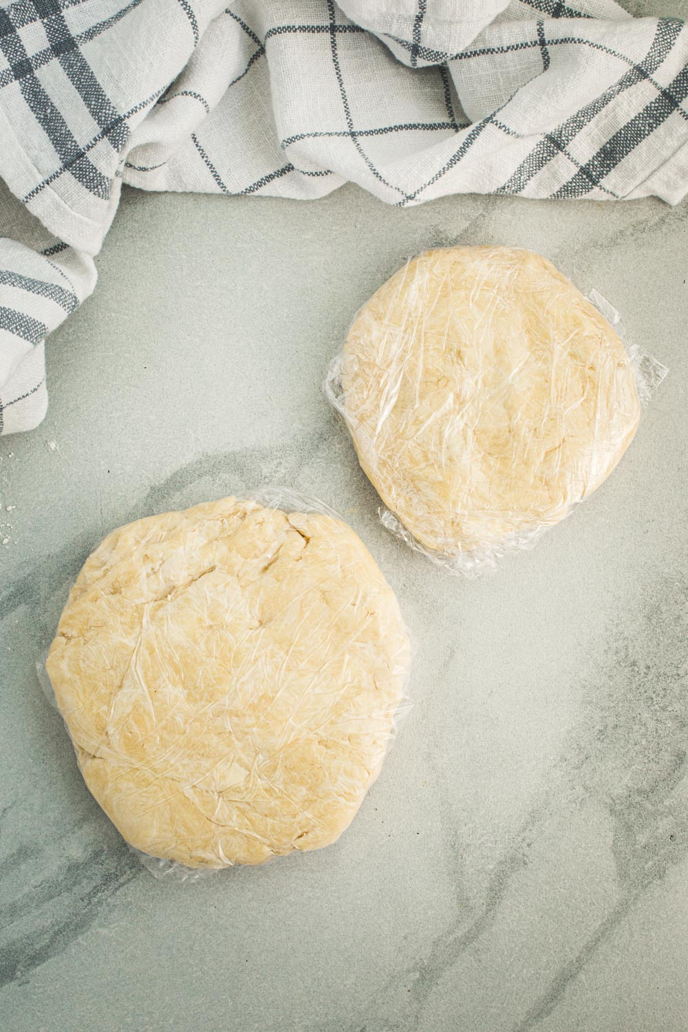 Flaky pie crust dough wrapped in plastic wrap.