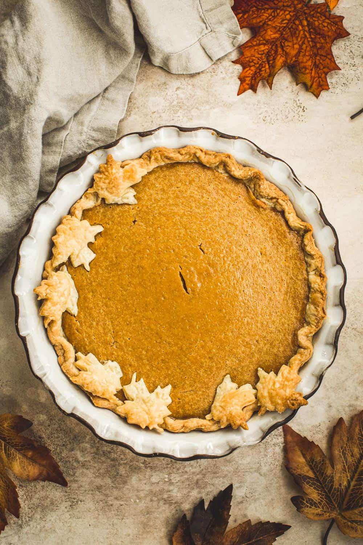 Whole pumpkin pie in a white pie dish with leaf pie crust design.