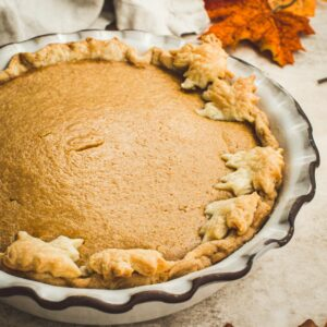 Maple pumpkin pie with a leaf cut out crust in a fluted pie dish.