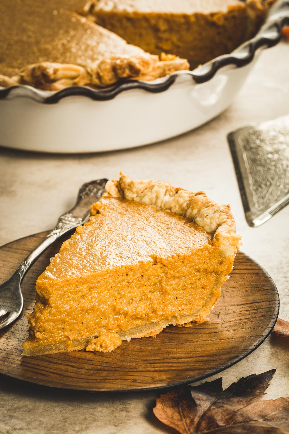 Maple pumpkin pie slice on a wooden plate with a silver fork.