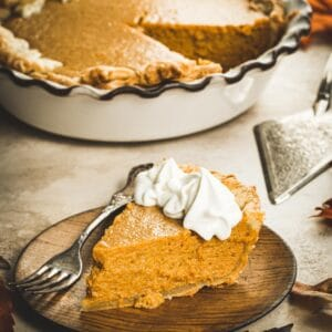 Slice of pumpkin pie on a wooden plate with a silver fork.