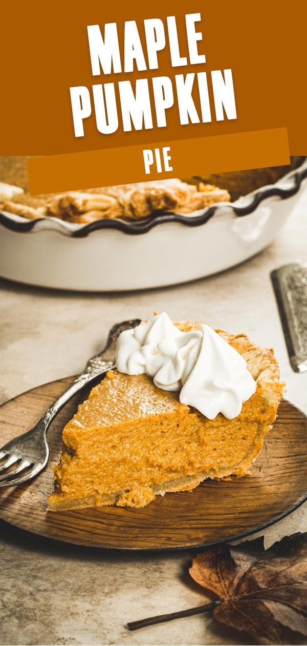 Maple pumpkin pie slice topped with whipped cream on a wooden plate.