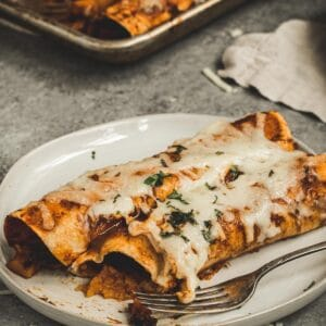 Butternut squash enchiladas on a plate with a fork.