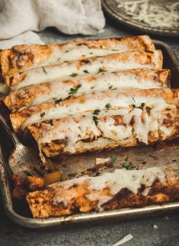 Butternut squash enchiladas on a rimmed baking sheet with a serving fork.