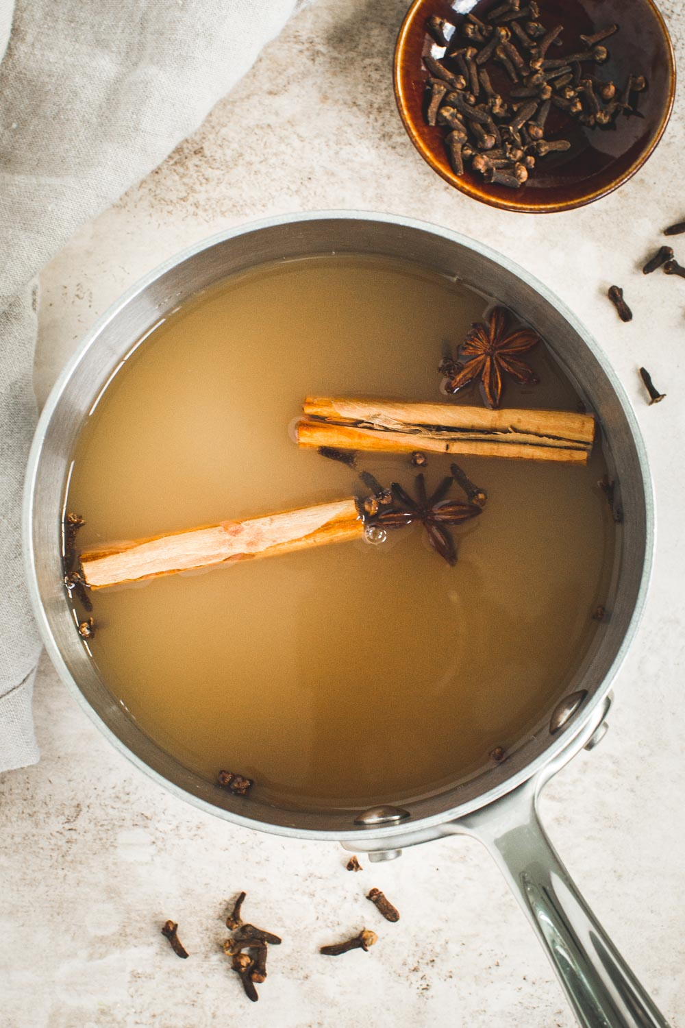Bourbon apple cider cocktail mixture in a large pot with cinnamon sticks.